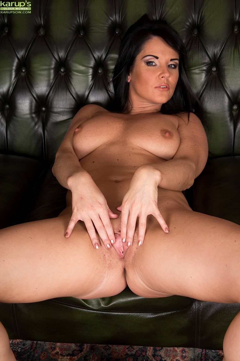 Curvy mature babe Danielle Leah Raven playing with her shaved pussy on the sofa at Karupsow