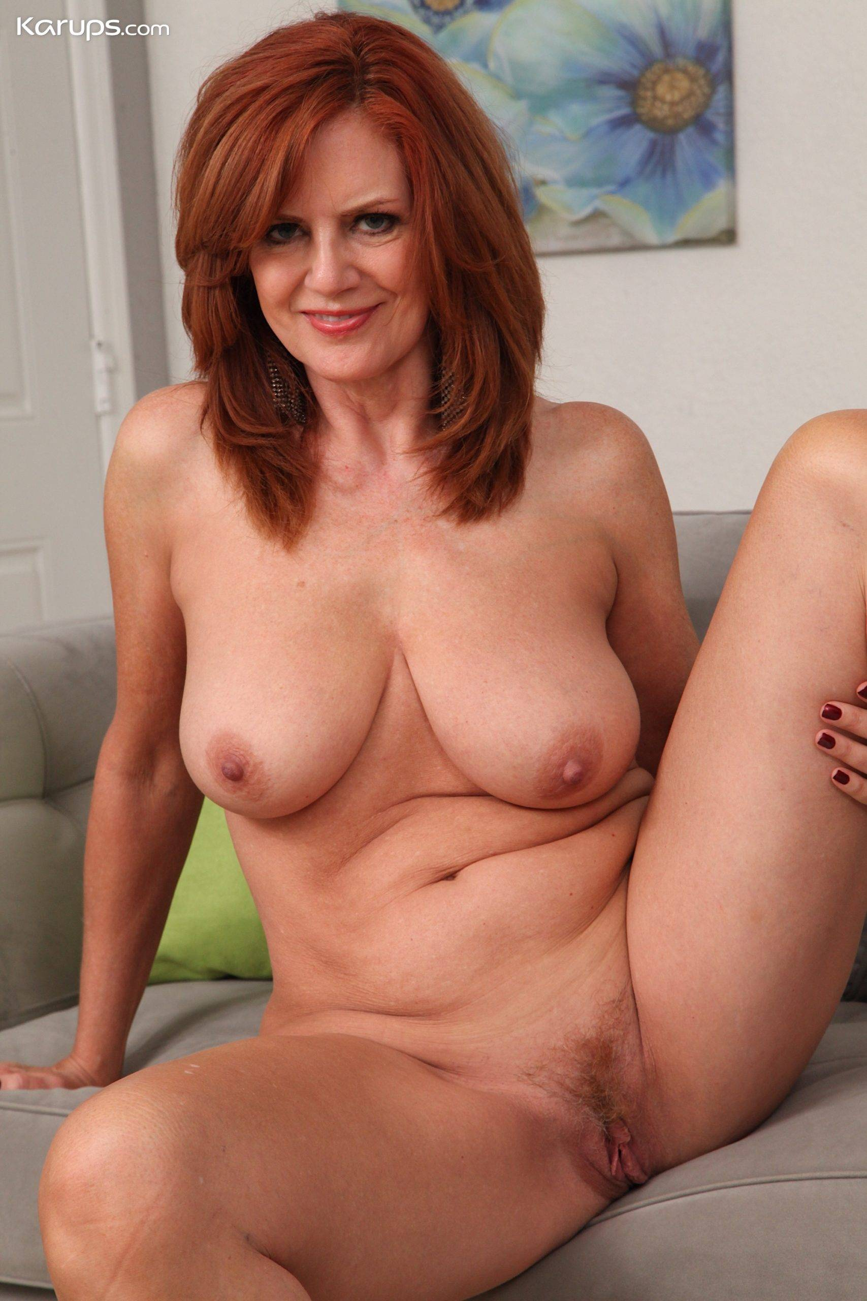 Sexy older redhead Andi James strips off all her clothes at Karupsow