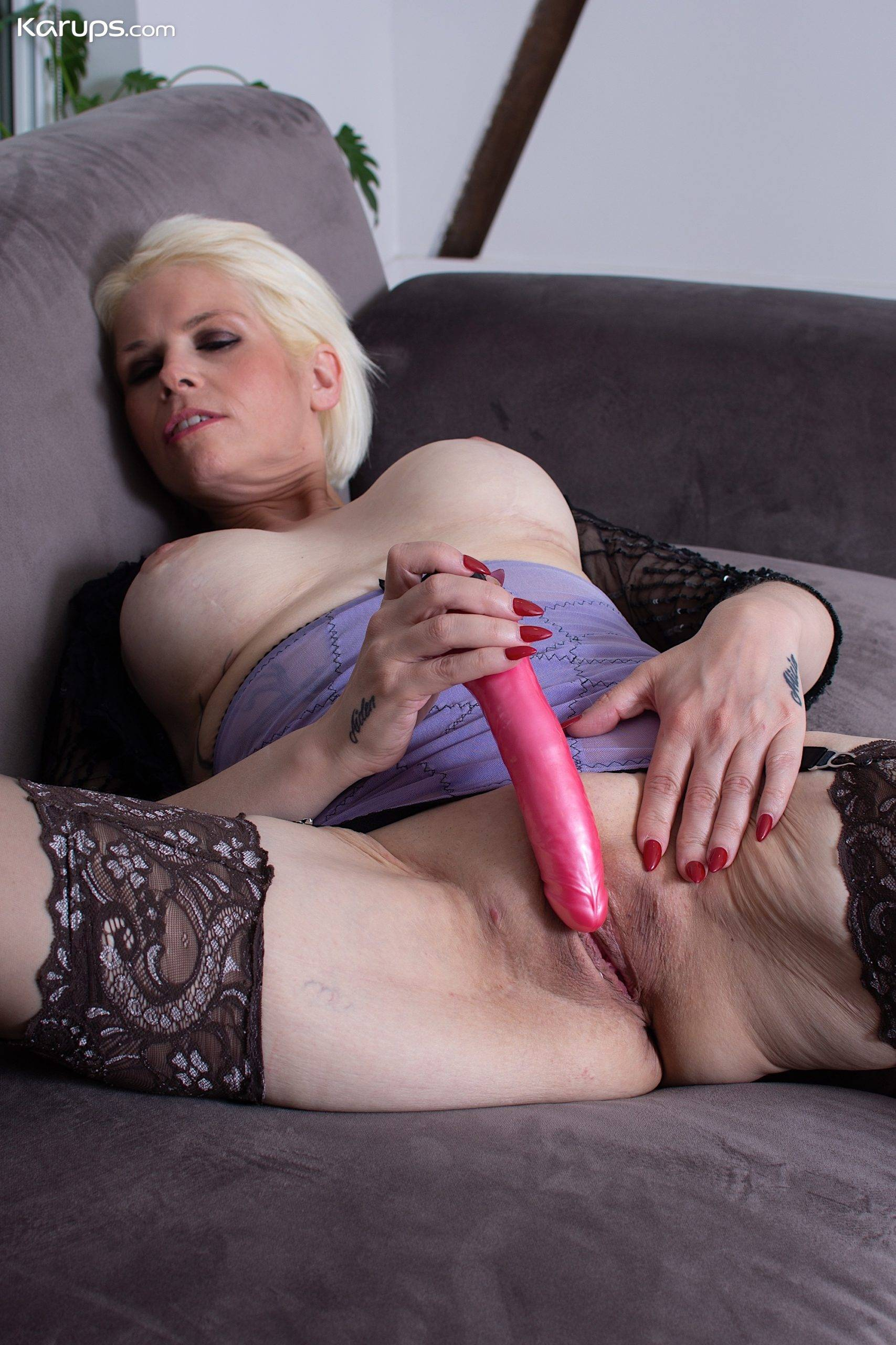 Busty mature babe Skyler Squirt toys her pussy on the couch at Karupsow